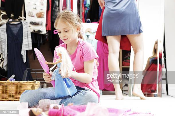 Girl on floor dressing doll, mum dressing behind