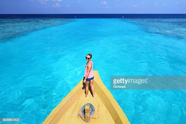 Girl on front of boat overlooking crystal clear water