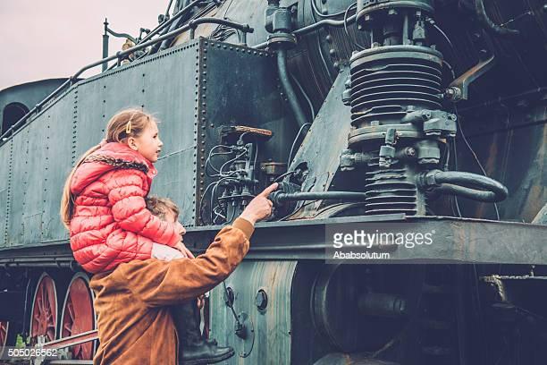 Ragazza su nonno s spalle osservare vecchia locomotiva a vapore, Europa