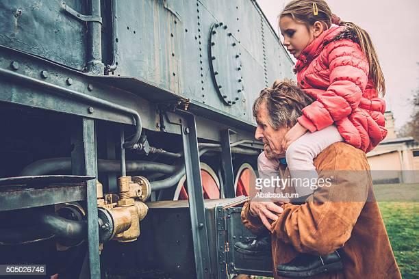 Girl on Grandfather's Shoulders Observing Old Steam Locomotive,  Europe