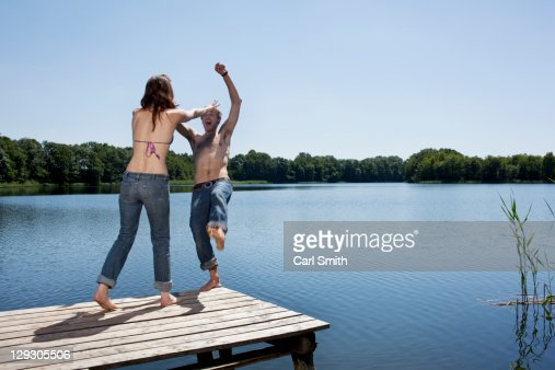 Girl on jetty pushes guy into water
