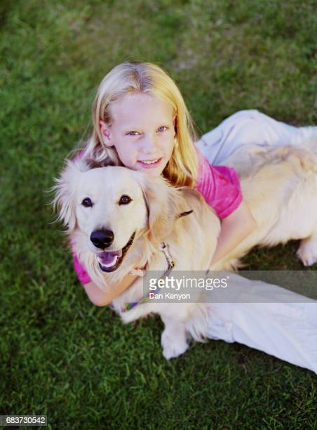 Girl on lawn with dog. Over head angle.