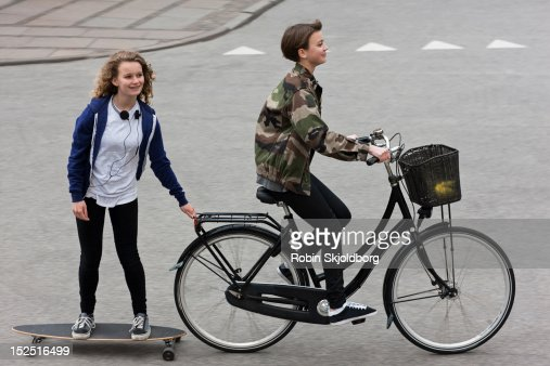 Girl on longboard pulled by girl on bike : Stock Photo