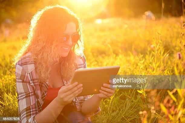 Fille sur la nature avec une tablette pour ordinateur portable