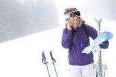 Girl on phone looking at map on ski slope