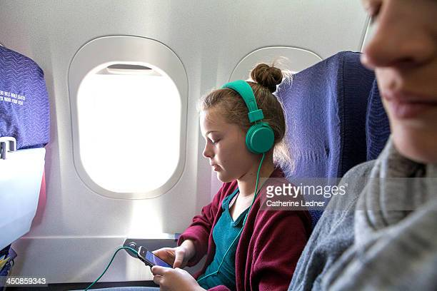 Girl on Plane listening to music with headphones