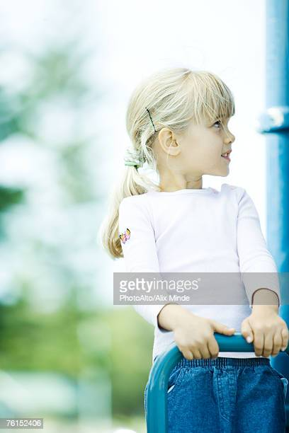 'Girl on playground equipment, looking up'