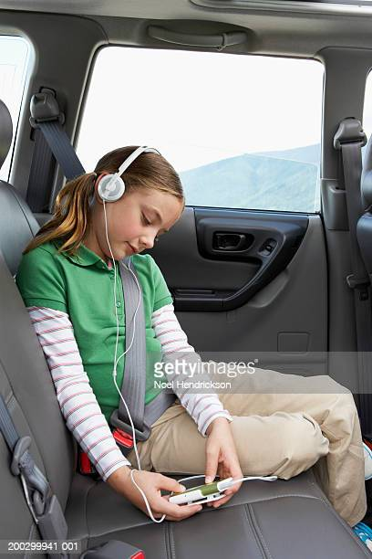 Girl (6-8 years) on rear seat of car, listening to portable MP3 player