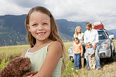 Girl (5-7 years) on road trip with family, smiling, portrait, close-up