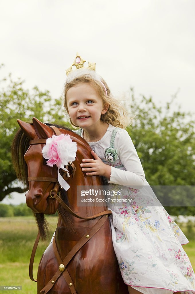 girl on rocking horse in field : Stock Photo