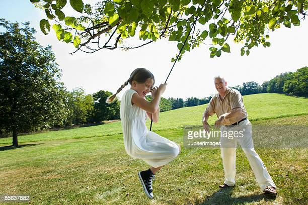 Girl on rope swing with grandfather