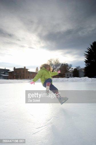 Girl (4-6) on skates falling on frozen lake, winter : Stock Photo