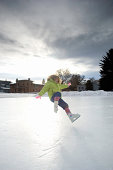 Girl (4-6) on skates falling on frozen lake, winter
