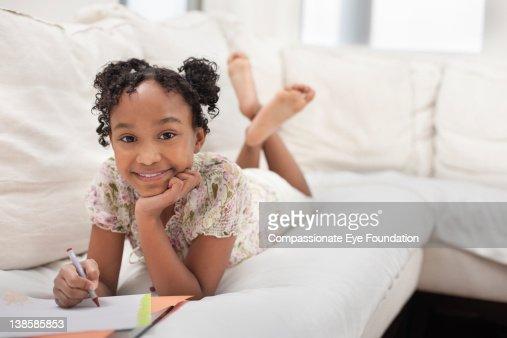 Girl on sofa doing homework