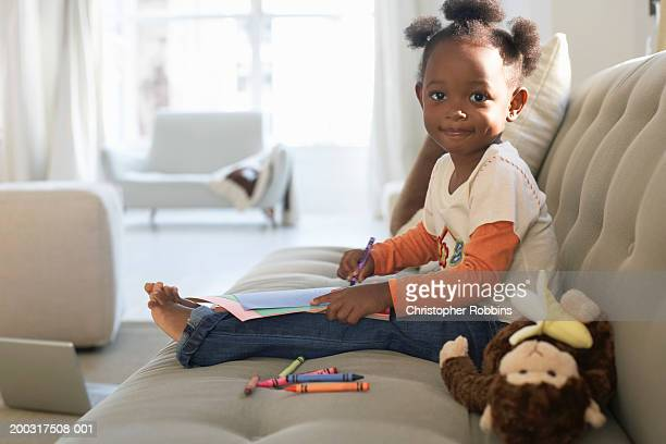 Girl (2-4) on sofa, holding crayon and paper, smiling, portrait