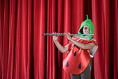 Girl on stage dressed as strawberry playing flute