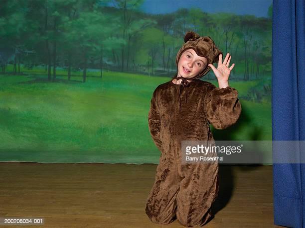 Girl (9-11) on stage wearing bear costume, waving