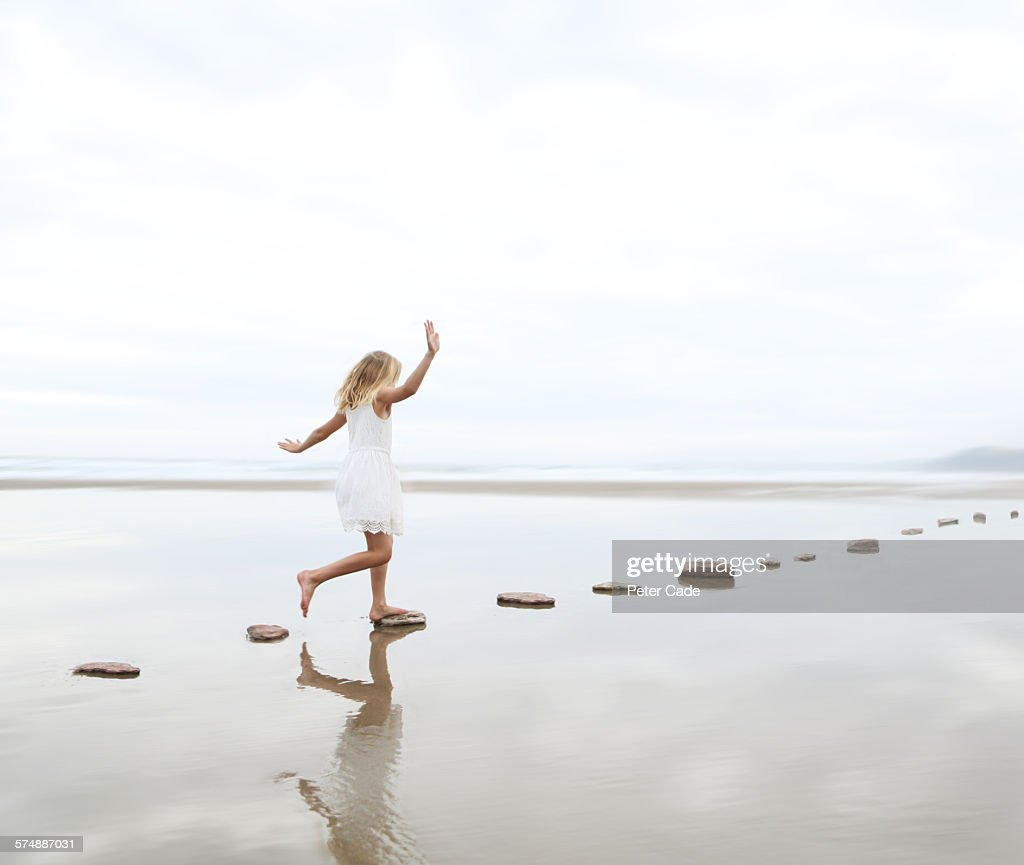 Girl on stepping stones on beach