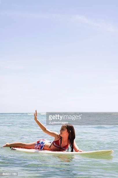 Girl on surfboard waving