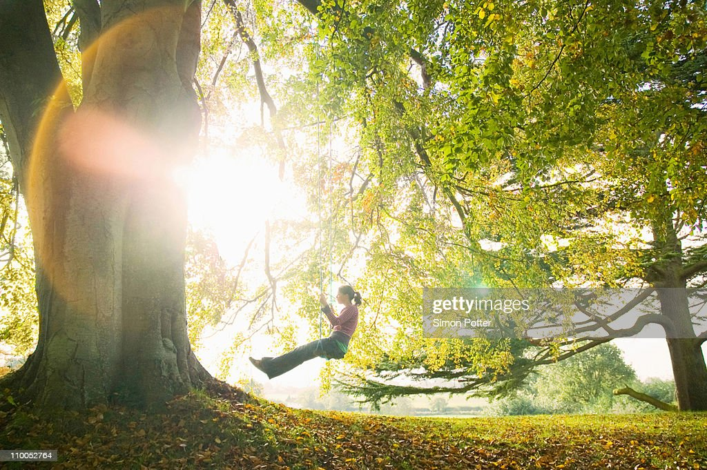 Girl on swing in sun : Stock Photo