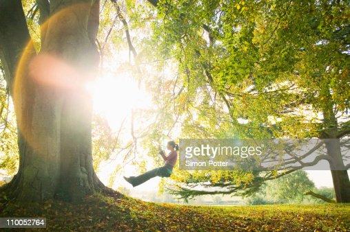 Girl on swing in sun : Stock Photo