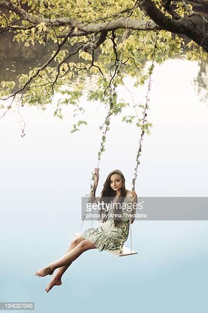 Girl on swing over lake