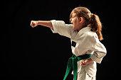 Little girl training martial arts against dark background. She wears white kimono with green belt