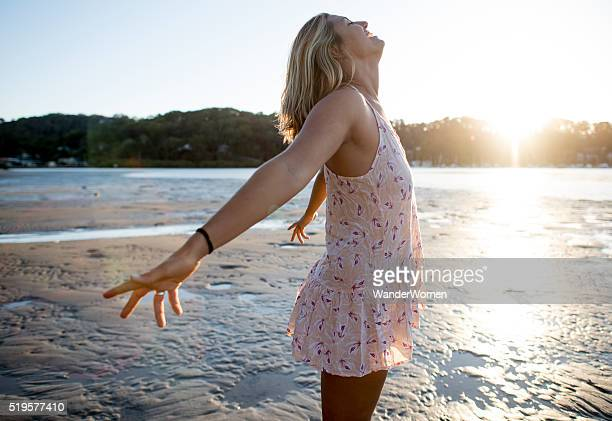 Girl on the beach dancing at sunset with sunflare