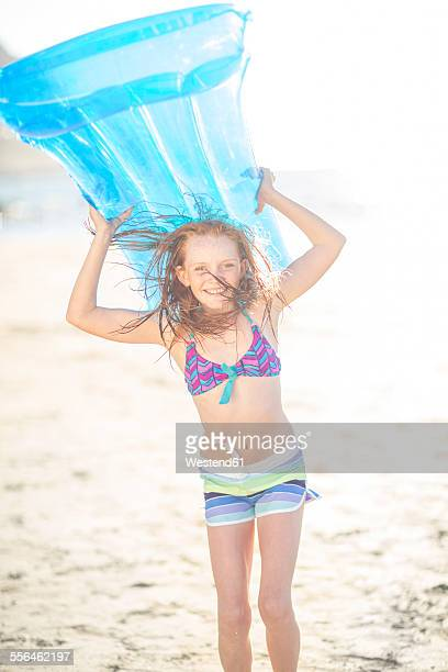 Girl on the beach smiling and holding a lilo
