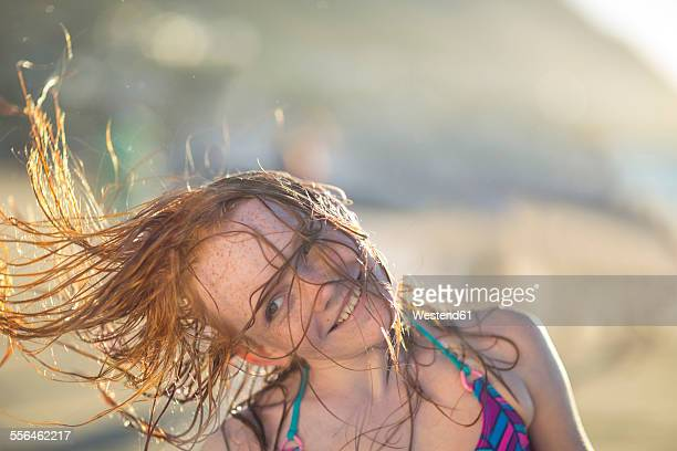Girl on the beach smiling and swinging her hair in the wind