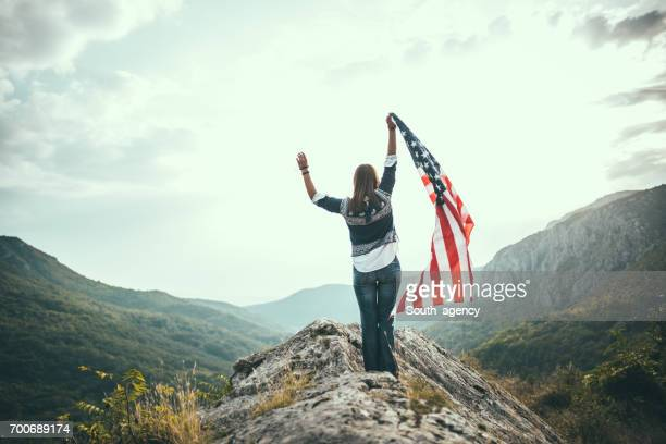 Jeune fille au sommet d'une montagne, tenant un drapeau américain