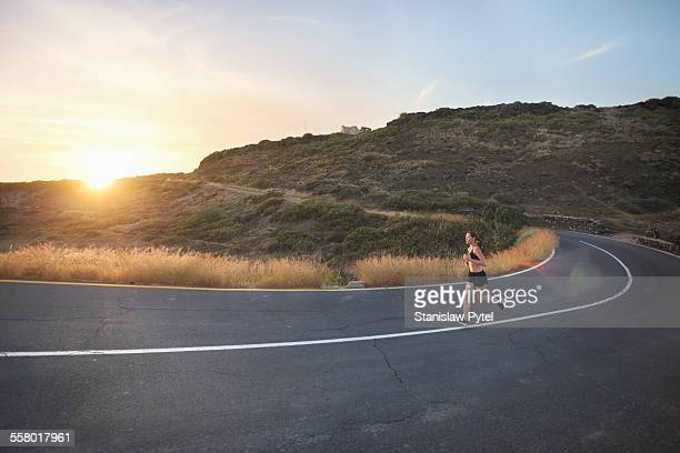 Girl on wild road taking curve , sunset