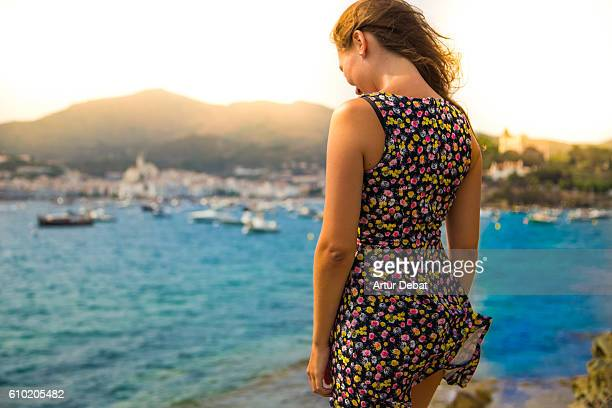 Girl on windy day contemplating the sunset in the Cap de Creus region in Costa Brava with good vibes on summertime.