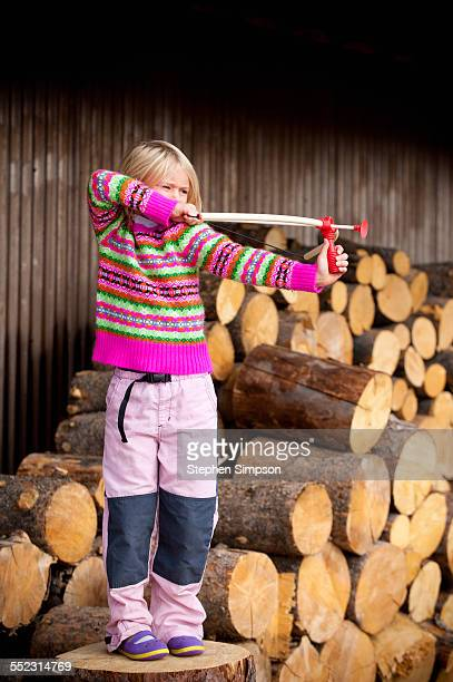 girl on wood pile with rubber-tipped bow & arrow