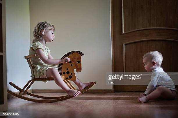 Girl on wood toy horse playing with her brother