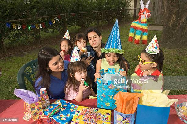 Girl opening gifts at birthday party outdoors