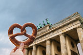 The girl is holding a delicious traditional German pretzel in the hand against the backdrop of the Brandenburg Gate in Berlin, Germany.