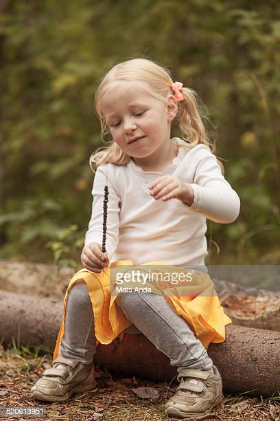 Girl outdoors putting bluberries on a straw