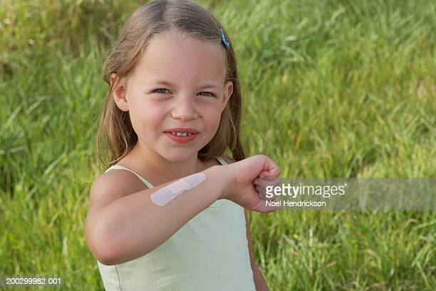 Girl (5-7 years) outdoors showing plaster on arm, portrait, close-up