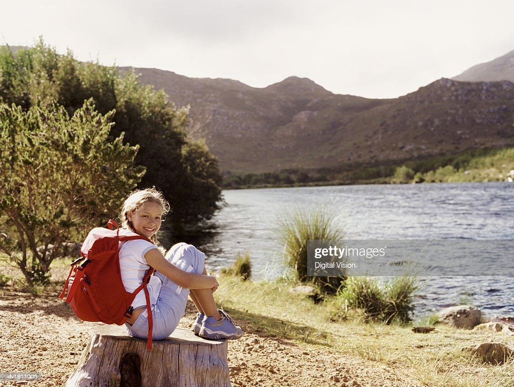 Girl Outdoors Sitting on a Tree Stump by a Lake : Stock Photo