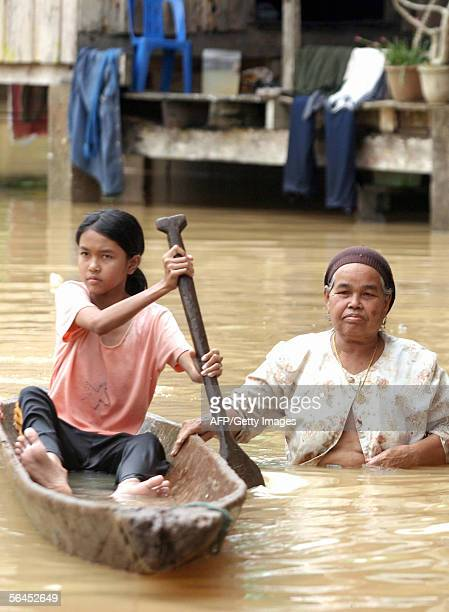A girl paddles a boat next to her mother during floods in Yala province 19 December 2005 The death toll from floods across southern Thailand since...