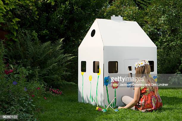A girl painting a cardboard wendy house