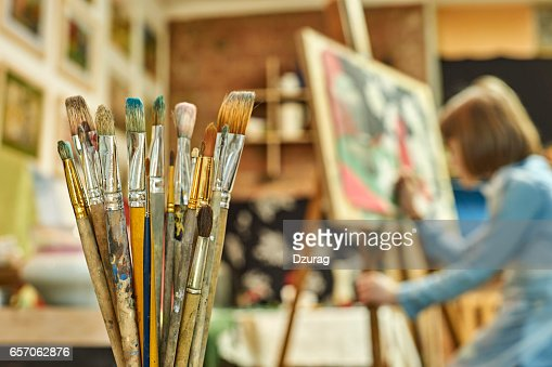 Girl painting a picture in art workshop : Stock Photo