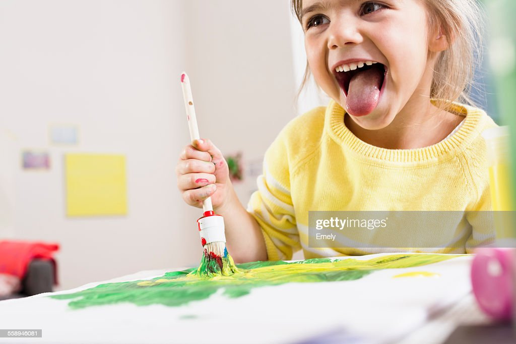 Girl painting and sticking out tongue : Stock Photo