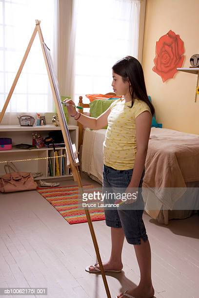 Girl (10-11) painting at easel, side view