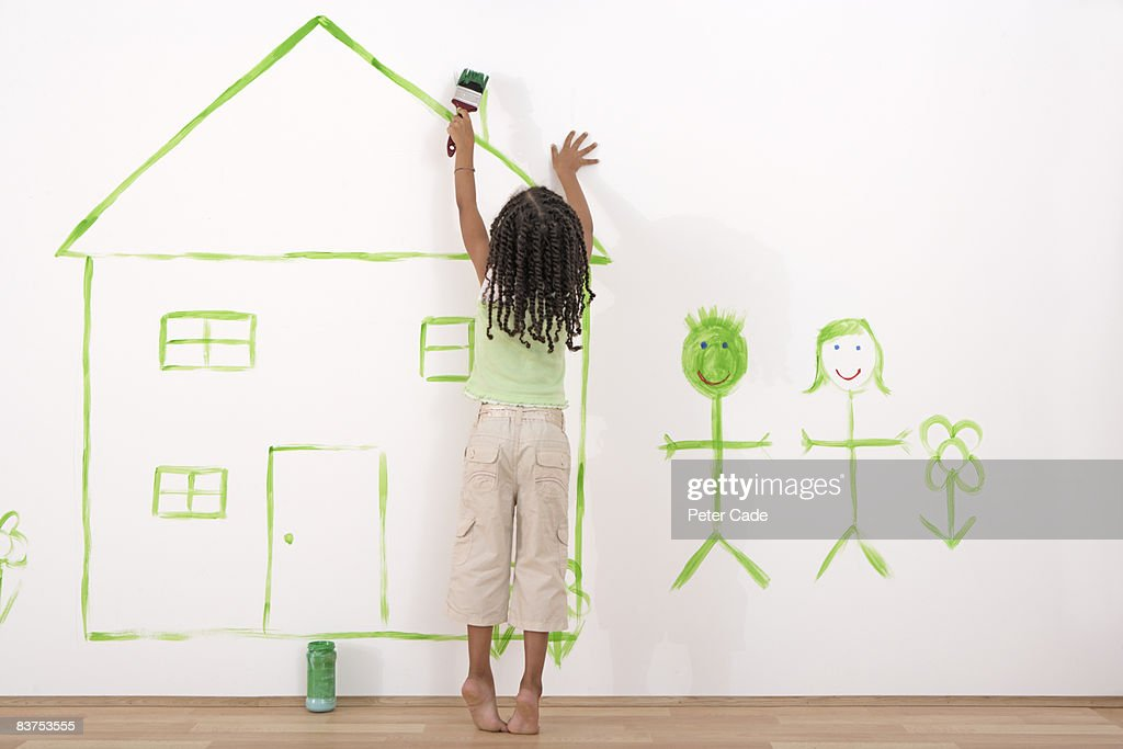 girl painting house on wall : Stock Photo