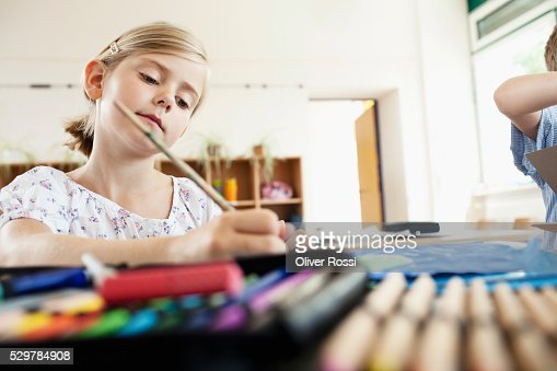 Girl painting in classroom : Stock Photo