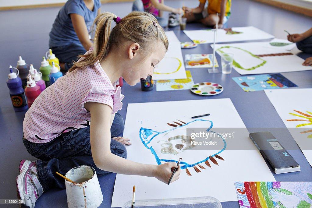 Girl painting in schoolclass