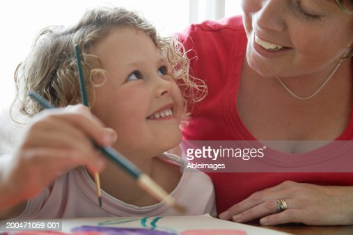 'Girl (3-5) painting picture, looking up at mother, smiling' : Stock Photo