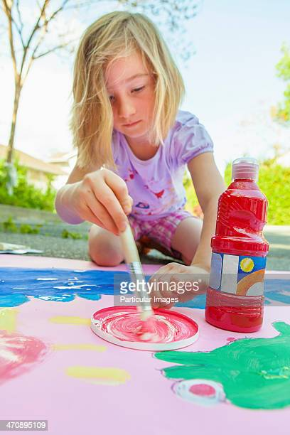 Girl painting with tempera on paper